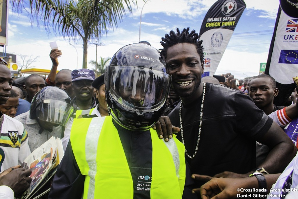 Bobi Wine gives a motorcyclist an autographed reflective vest for following proper road safety