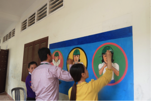 Manulife Cambodia and AIP Foundation staff paint road safety murals at Vealvong Primary School.