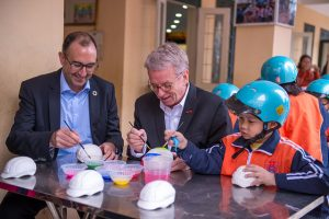 "Saul Billingsley, Executive Director of the FIA Foundation, and Greig Craft, President of AIP Foundation, paint helmet sculptures with students as part of activities for the ""Fun with Traffic Safety"" Day."