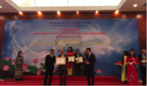 Mr Don Tuan Phong, Vice chairman of VUFO (left), and Mr. Phan Anh Son, Director General of PACCOM (right), present President Greig Craft with an award.