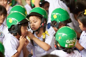 A student from Wat Chong Nonsi School assists her classmate with putting on her new helmet through our Helmet for Kids program.