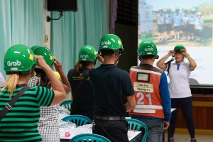 Staff demonstrate how to wear a helmet correctly to parents at Wat Chong Nonsi School.