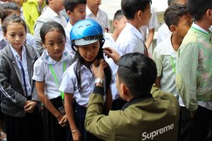 A road safety ambassador assists a student with putting on her new helmet.