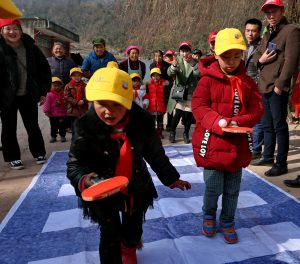 Students at Huazhu Primary School participate in interactive games to practice road safety skills.