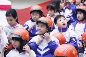 A student follows instructions on how to properly buckle his helmet during a demonstration at the ceremony.