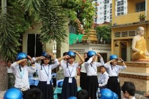 Students from Wat Toul Tompong Primary School use the two finger rule to measure the correct positioning of their helmets.