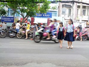 Two students cross a busy road on their way to school in Ho Chi Minh City.