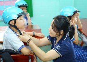 An Abbott volunteer adjusts the helmet for a student from Tan Thanh Dong Primary School, which participates in our Helmets for Kids program.