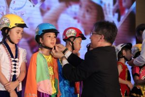 A stakeholder at the announcement ceremony assists a first grade student with putting on her new helmet.