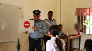 Police officer teaches important road safety signs to a student at Veal Vong Primary School.