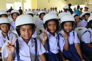 Students wearing their new helmets at the launch ceremony for Helmets for Kids.