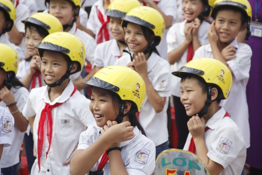 Primary school children in Thai Nguyen learn the three steps to wearing a helmet for the first time